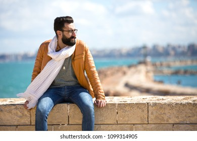 Close shot of a handsome man wearing a winter outfit and sitting on a stone fence looking away