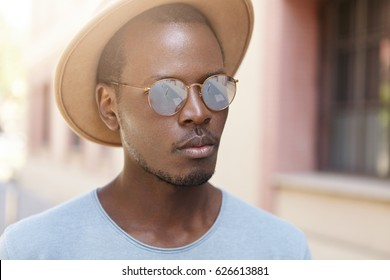 Close up shot of handsome young African American traveler having nice walk in old town during summer vacations. Black man wearing stylish mirrored lens sunglasses and hat standing in urban setting