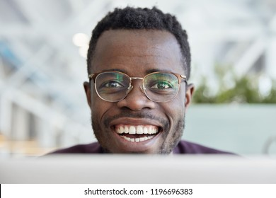 Close up shot of happy dark skinned man with broad smile, white teeth, wears transparent glasses for good vision, satisfied with work, being in good mood, poses indoor. People and positive emotions
