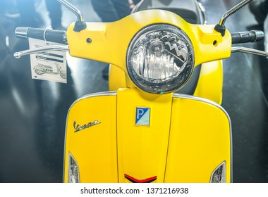 A close up shot of the headlight and logo of a Yellow Vespa Scooter. Vespa is an Italian brand of scooter manufactured by Piaggio. International Motorcycle Exhibition, Istanbul 2019.