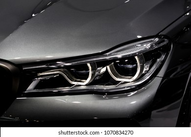 Close up shot of headlight in luxury  grey car background. Modern and expensive sport car concept