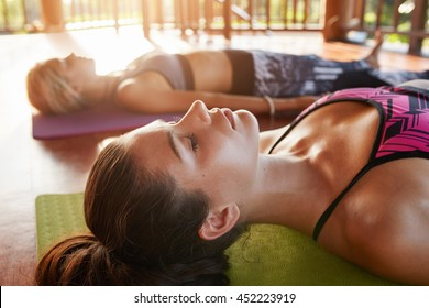 Close up shot of healthy young woman lying on floor. Young people relaxing in savasana pose at yoga class.