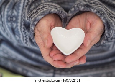Close up shot of a heart shaped white ceramic in the hands of an elderly woman. Heart and Health care concept