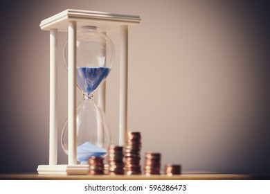 Close up shot of hourglass and coins with blank background. Business Finance and Money concept,Time is money. Vintage process style.