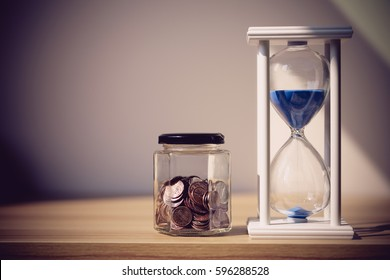 Close up shot of hourglass and coins with bokeh background. Business Finance and Money concept,Time is money. Vintage process style.