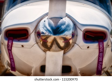 A close up shot of the hub and spinner of an airplane propeller with the ground in front of the plane reflected in the polished spinner.