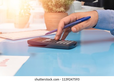Close up shot of human hand over calculator