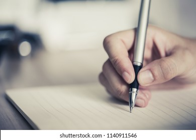 Close shot of a human hand writing something on the paper.