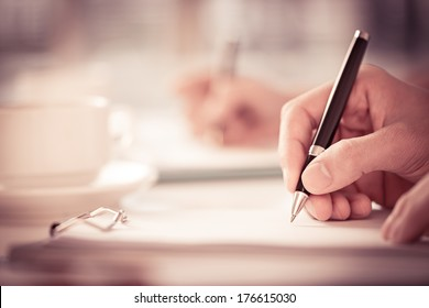 Close shot of a human hand writing something on the paper on the foreground