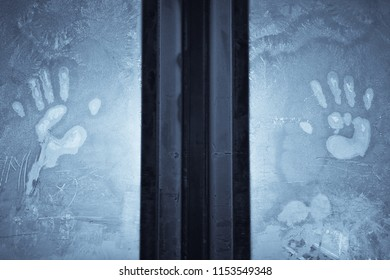 Close up shot of a human palms imprint on a frosty window.