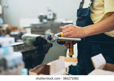 Close up shot of industry worker holding a electric drill.