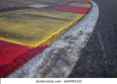 Close shot to the inside of the famous Eau Rouge curve at Spa Francorchamps, marked with red and yellow curbs. the black marks ar rubber deposit on the paint.