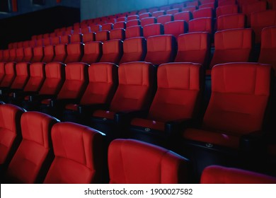 Close up shot of interior of cinema auditorium with lines of red chairs. Horizontal shot