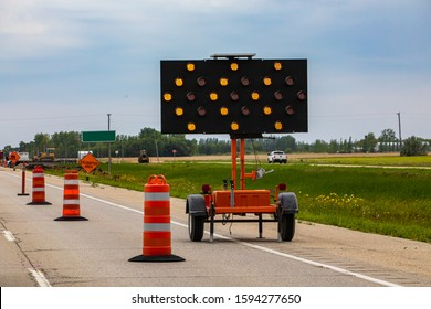 A close up shot of an LED mobile matrix keep left sign, with orange flashing lights warning motorists with arrows and road cones during lane closure