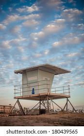 A close up shot of a life guard tower in Huntington Beach with a cloudy blue sky.