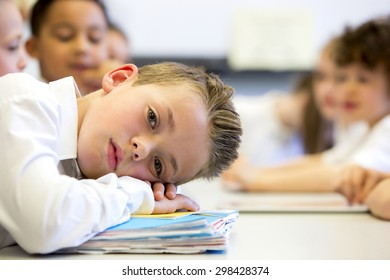A close up shot of a little boy at school who looks distant and upset.