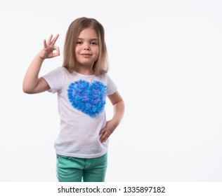Close up shot of little positive girl with long fair hair looking at camera artistically and shows ok-gesture. The portrait is made on a white background.