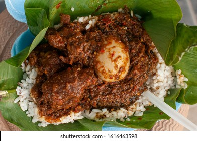 A close up shot of local rice Ofada being served with egg, beef and smoked fish - Shutterstock ID 1616463598