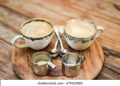 Close up shot looking down at two cups of coffee, on a wood cutting board with milk, sugar and two spoons. They are on a wood table, in ceramic cups. This was shot in a cafe in Chiang Mai, Thailand.