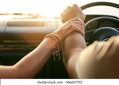 Close up shot of loving couple traveling by car and holding hands. Focus on hands of man and woman in a road trip.