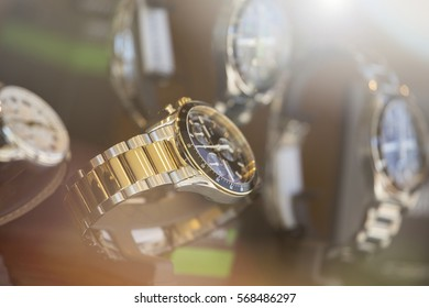 Close up shot of a luxury men watch. Lens flare in background.