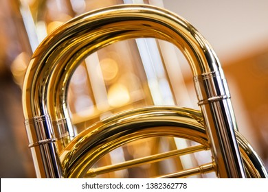 A close up shot of the main tuning slide of a Professional Bass Trombone with a line of trombones in the background out of focus with a bokeh background. Very warm tones of brass.