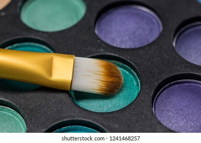Close up shot of makeup brush on colorful palette