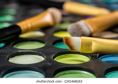Close up shot of makeup brushes on colorful palette