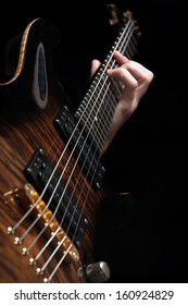 close up shot of male hand playing vintage brown guitar over black - shallow DOF with focus placed on strings