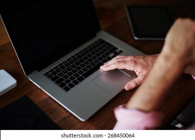 Close up shot with male hands on digital computer keyboard at wooden table in home interior, man use laptop sitting at wooden desk with hand against his mouth, soft focus, cross process image