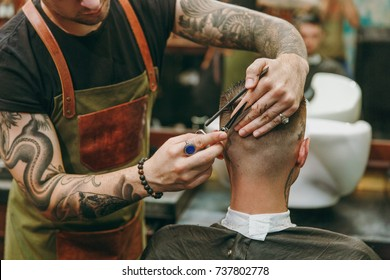 Close up shot of man getting trendy haircut at barber shop. The male hairstylist in tattoos serving client.