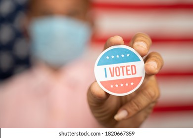 Close up shot man in medical mask showing I voted Sticker and putting on shirt with US flag as background - concept of US election
