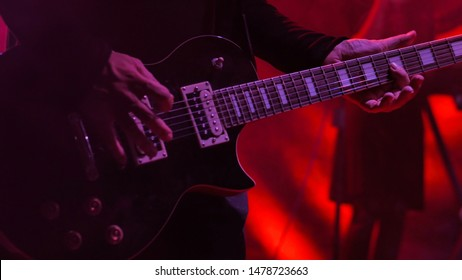 Close up shot of man playing guitar on concert stage. Entertainment and art concept