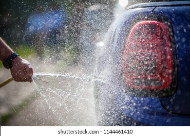 Close up shot of a man washing a car.
