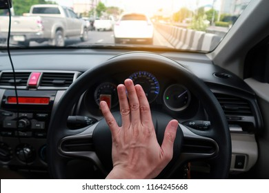 Close up shot of a man's hands holding a car's steering wheel and honking the horn with traffic jam