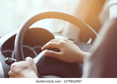 Close up shot of a man's hands holding a car's steering wheel and honking the horn on the road. Horn in car