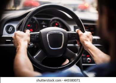 Close up shot of a man's hands holding a car's steering wheel.