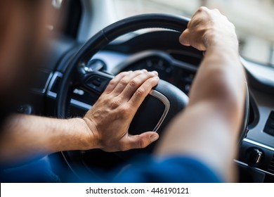 Close up shot of a man's hands holding a car's steering wheel and honking the horn.