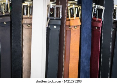 Close up shot of many leather belts of various colors.
