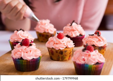 Close shot of many sweet cupcakes on the foreground while a baker decorating the last one
