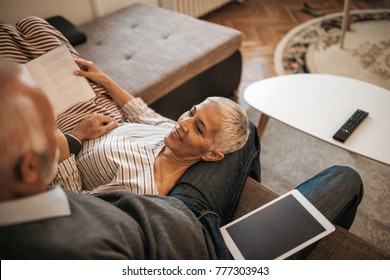 Close up shot of a mature woman lying in her husband's lap, reading a book