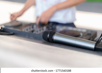 Close up shot of a microphone next to DJ playing music at outdoor event. Mic next to deejay mixing at the party