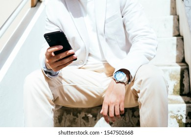 Close up shot of mobile in right hand and watch on left wrist of a man who sitting at the stair.