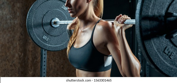 Close up shot of Muscular young woman doing weightlifting at gym Crossfit Workout with the barbells Female bodybuilder doing back squats in gym Fit Woman Doing Barbell Squats In The Gym.