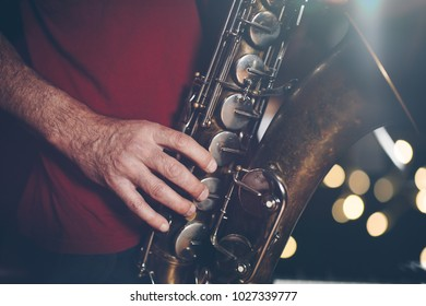 Close up shot of musician playing saxophone. Low light and selective focus.