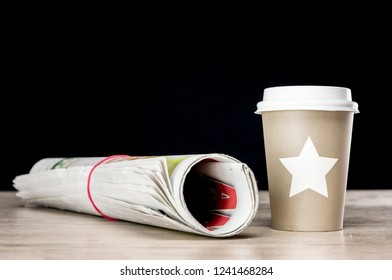Close up shot of a newspaper and cap of coffee