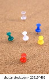 A close up shot of a notice board pins