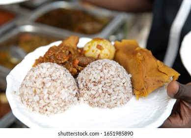 A close up shot of Ofada rice served with moin moin, boiled egg and obe dindin sauce - Shutterstock ID 1651985890