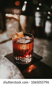 A close up shot of Old Fashioned, whisky based cocktail with ice cubes on a black napkin at the bar. Perfect way to end the week, vertical image, cocktails concept.
