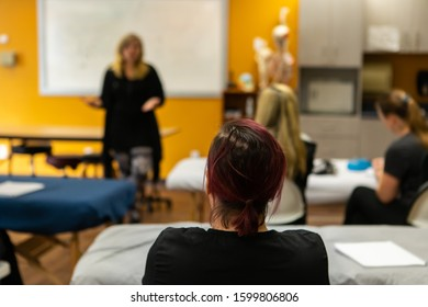 A close up shot on the back of a female head with red hair, woman listens to teacher give anatomy class, with blurry class in background and copy space